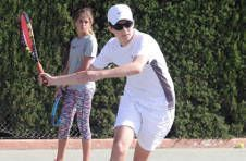 Thumbnail an ISC monitor and students practising their tennis forehands in Spain